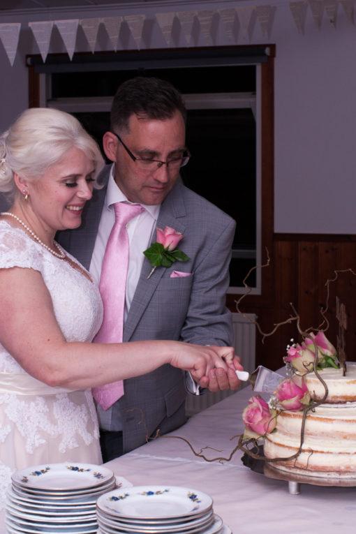 En bröllopsfotografering i Smålands djupa skogar!- Brudparet skär första biten ur tårtan!   www.photobymj.se